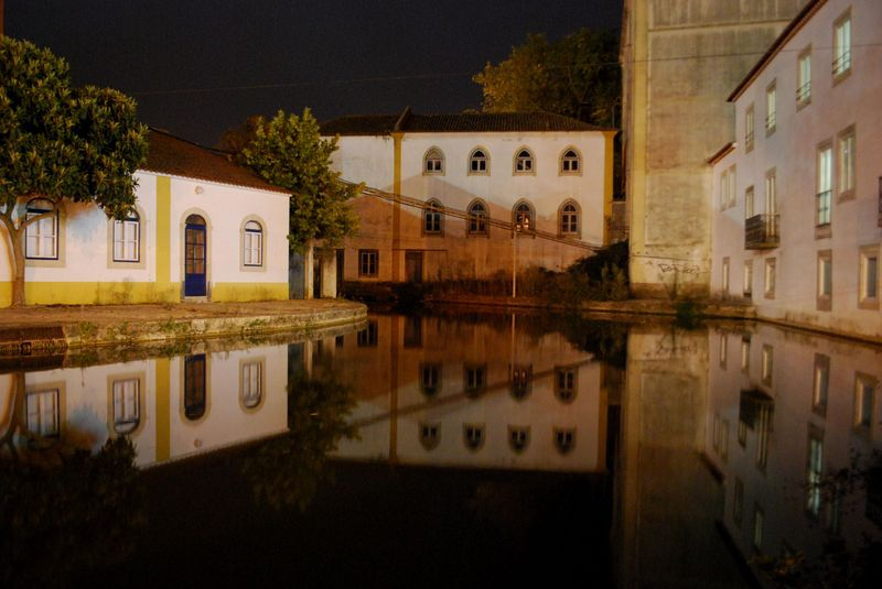 Buildings reflecting on the waters of Nabão River