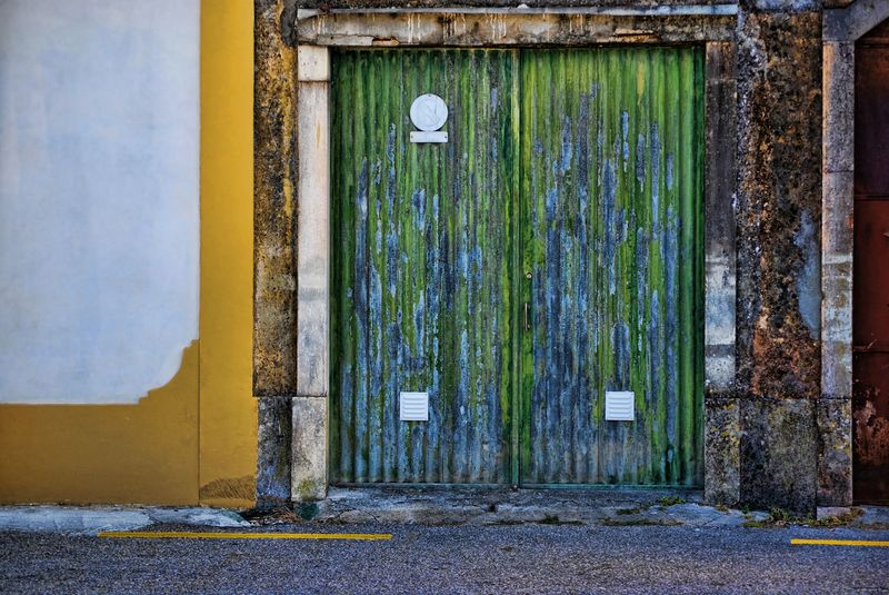 Decayed green door in the City of Tomar in Portugal