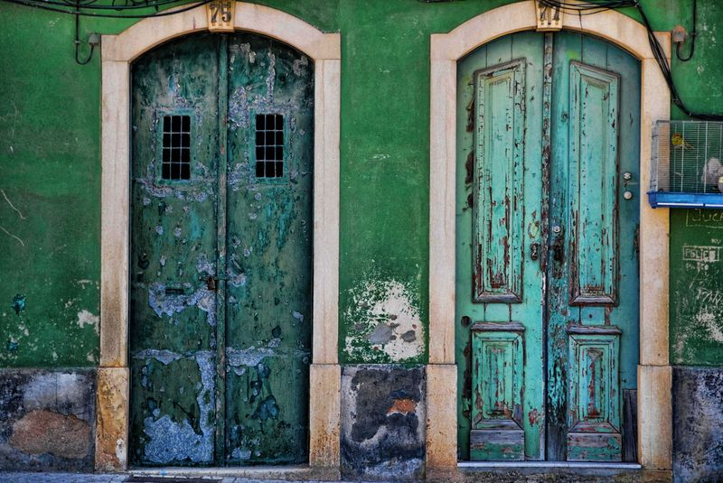 Old, decaying green doors and walls in the City of Tomar