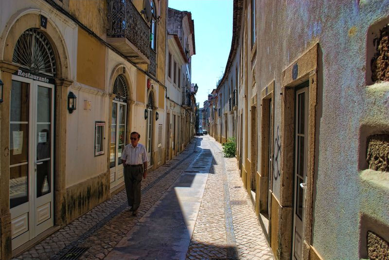 Gentleman walking in an old street of the City of Tomar in Portugal