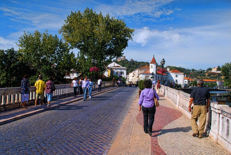 People crossing the Old Bridge of the City of Tomar in Portugal