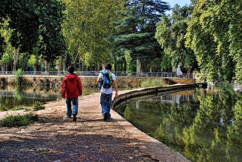 Teenagers crossing a small dam at Nabão River in the City of Tomar in Portugal