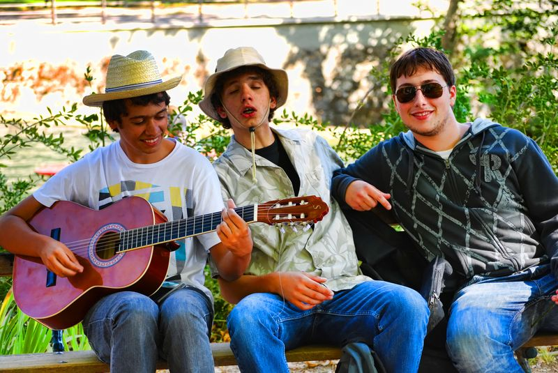 Teenagers with a guitar at Mouchão Park in the city of Tomar