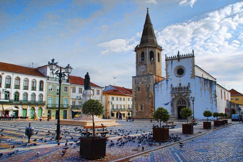 Church, statue and pigeons at Praça da República in the City of Tomar