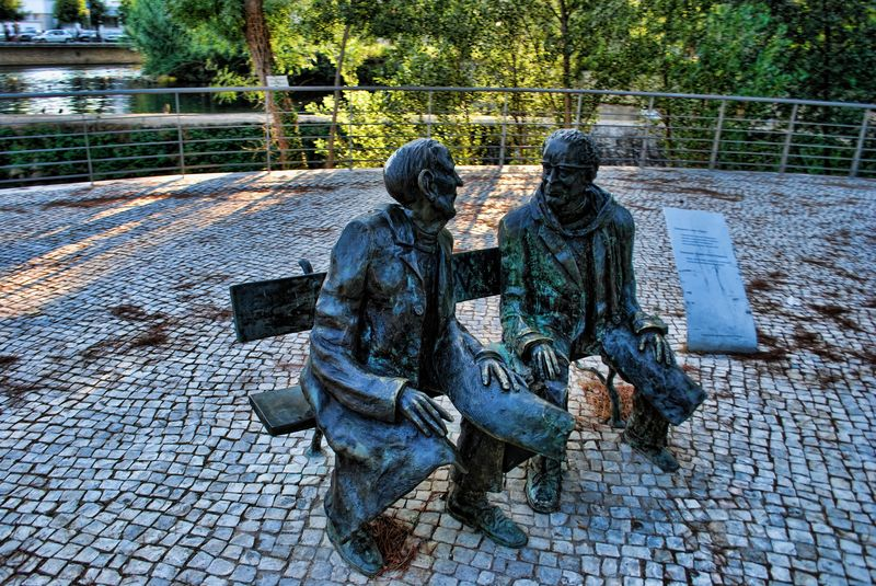 Statues of Nini Ferreira and Lopes Graça on a bench at Mouchão Park