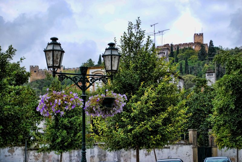 Flowers hanging baskets and the Castle of the Knights Templar in Tomar