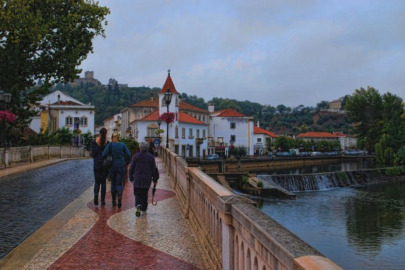 Crossing the old bridge in a rainy day in the City of Tomar in Portugal